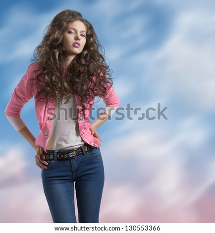 attractive young spring girl with pink jacket and curly hair with a colorful background - stock photo