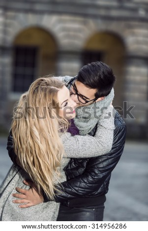 Attractive young stylish couple in love outdoors. Man kisses his girlfriend