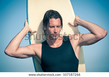 Attractive young surf man portrait at the beach with a surfboard. - stock photo