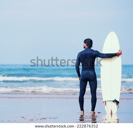 Attractive young surfer holding surfboard while standing on the beach looking at ocean to find the perfect spot to go surfing waves,professional surfer with surf board looking at ocean, filtered image - stock photo