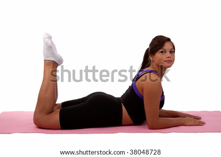 Attractive young teen aboriginal ethnicity brunette girl wearing fitness attire laying flat on stomach with legs bent on a pink yoga mat over white - stock photo