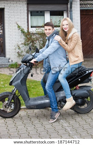 Attractive young teenage couple sitting on a motorcycle together parked on the driveway outside their house smiling happily at the camera