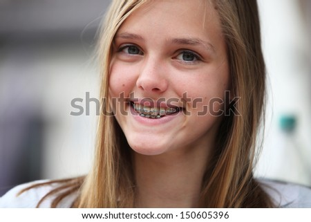 Attractive young teenage girl with orthodontic braces on her upper and lower teeth smiling for the camera - stock photo