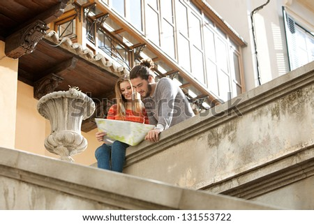 Attractive young tourist couple sitting on top of an old city stairs looking at an open street map while on holiday. - stock photo