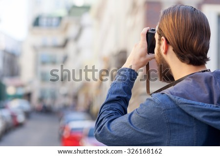Attractive young tourist is photographing city with inspiration. He is standing and holding camera. Copy space in left side - stock photo
