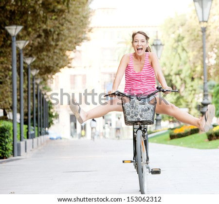 Attractive young tourist woman visiting a destination city and riding a bike in a wide avenue, stretching her legs and having a fun and excitement expression, outdoors. - stock photo