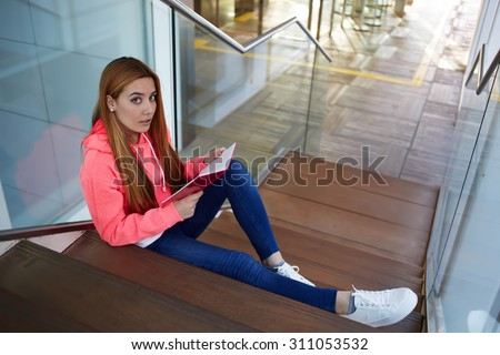 Attractive young university student preparing for the exam while reading her notepad at campus interior, stylish hipster girl resting after classes sitting on the stairs in the hallway of university - stock photo