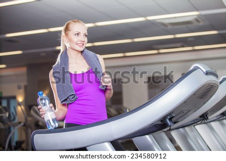 Attractive young woman after running on a treadmill, exercise at the fitness club  - stock photo
