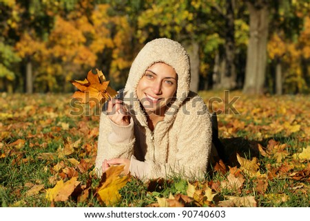 Attractive young woman against autumn leaves. Outdoor shot - stock photo