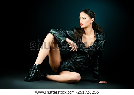 Attractive young woman alluring in fitting leather suit. Beauty, fashion. Full length portrait. - stock photo