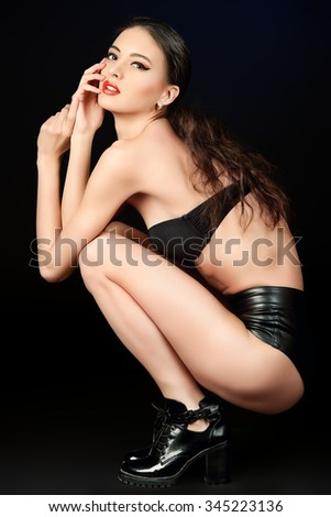 Attractive young woman alluring in fitting leather suit, underwear. Beauty, fashion. Full length portrait. - stock photo
