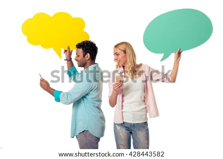 Attractive young woman and Afro American man with speech bubbles are using phones and smiling, standing back to back on white background - stock photo