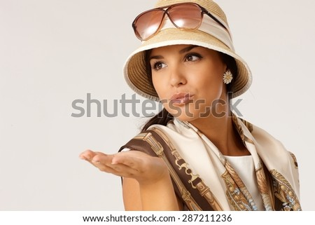 Attractive young woman blowing a kiss at summertime, wearing hat, looking away. - stock photo