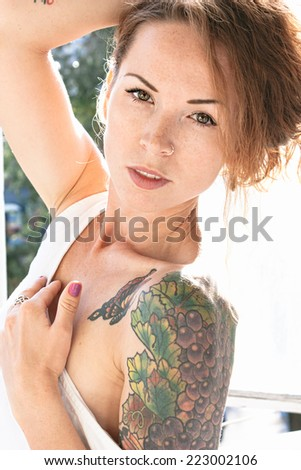 Attractive young woman displaying a colorful arm tattoo as she lowers the shoulder of her summer top - stock photo