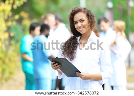 Attractive young woman doctor with clipboard in hands against group of medics, outdoors - stock photo
