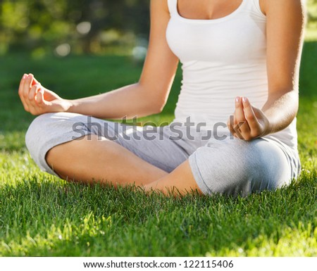 Attractive young woman doing yoga. Focus on hand - stock photo