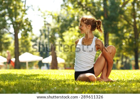 Attractive young woman doing yoga in park.
