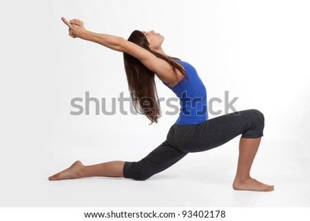 Attractive young woman doing Yoga Warrior Pose - stock photo