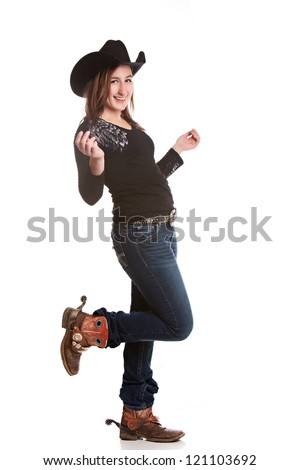 Attractive young woman dressed in a cowboy hat and boots with spurs, dancing.  Isolated on white. - stock photo