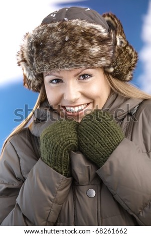 Attractive young woman dressed up warm in coat, fur-hat and gloves, smiling, freezing.?