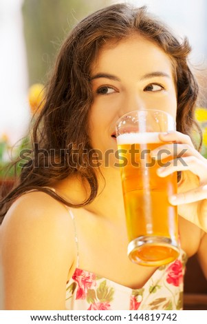Attractive young woman drinking beer on sidewalk cafe. - stock photo