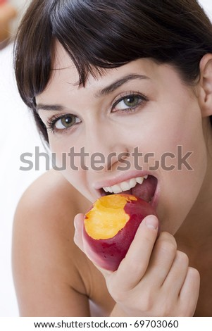 attractive young woman eating fresh nectarine and smiling - stock photo
