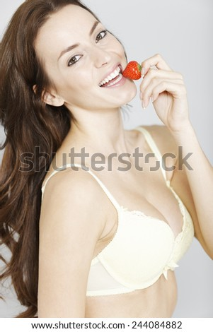 Attractive young woman enjoying a fresh strawberry in her underwear while getting dressed - stock photo