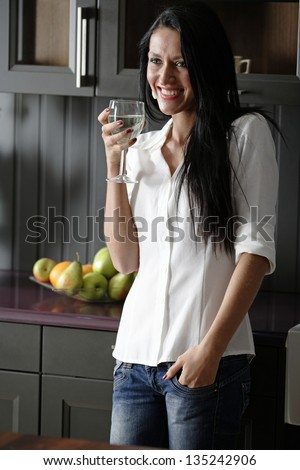 Attractive young woman enjoying a glass of wine in her kitchen.