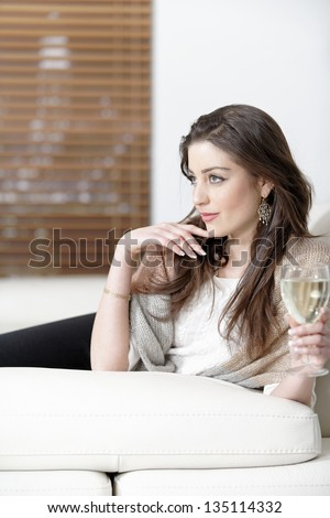 Attractive young woman enjoying a glass of wine on her sofa. - stock photo