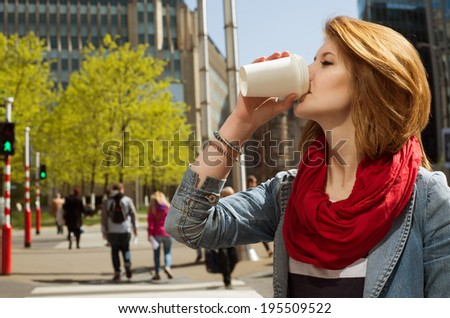 Attractive young woman enjoying a hot drink in a white paper cup against cityscape background - stock photo