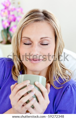 Attractive young woman enjoying her coffee with closed eyes at home