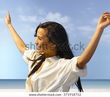 Attractive young woman enjoying summer holiday on the beach, laughing arms wide open. - stock photo