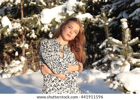 Attractive young woman freezes in the winter pine forest.  - stock photo