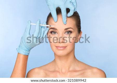 Attractive young woman gets cosmetic injection. Doctors hands making an injection in face. Beauty Treatment. - stock photo