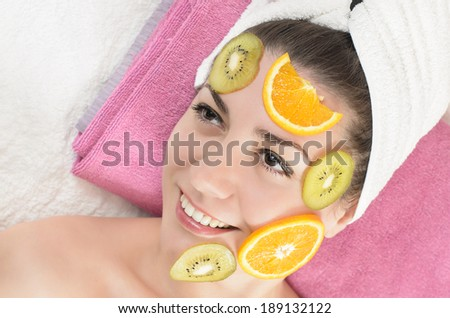 Attractive young woman getting a fruits facial mask in the beauty spa - stock photo