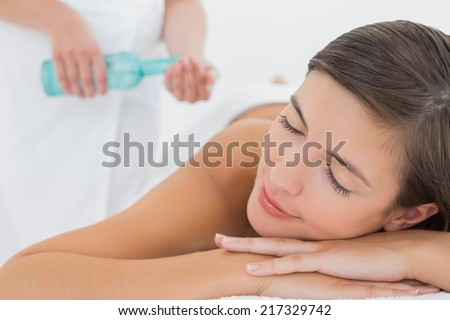 Attractive young woman getting massage oil on her back at spa center - stock photo