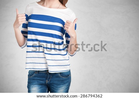 Attractive young woman giving the thumbs-up, isolated on a grey background - stock photo