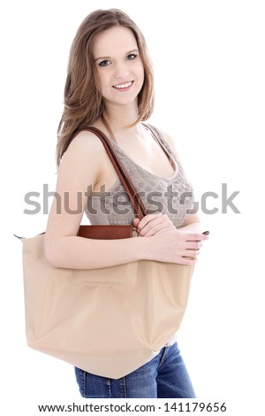 Attractive young woman going shopping carrying a large cloth bag over her shoulder standing sideways smiling at the camera, on white