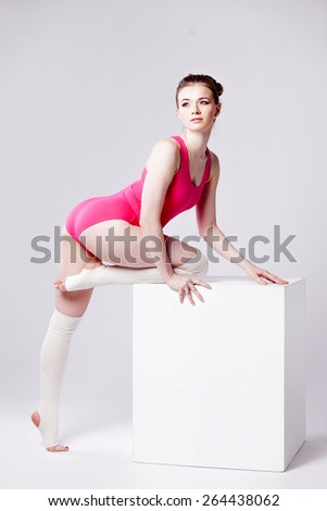 attractive young woman gymnast on  white cube, in a pink leotard - stock photo