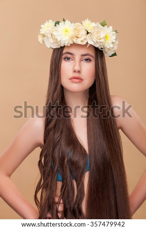 Attractive young woman has curly and smooth hair on different sides. She is standing with a flower wreath on her head. The lady is looking at camera confidently. Isolated - stock photo