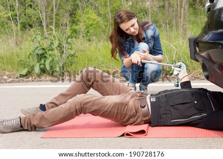 Attractive young woman helping a mechanic handing him his tools as he works under the engine compartment of her car following a roadside breakdown - stock photo