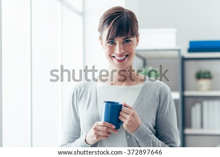 Attractive young woman holding a mug and having an hot coffee next to a window, she is smiling at camera - stock photo