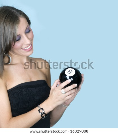 Attractive young woman holding an 8-ball looking for answer to her question. - stock photo