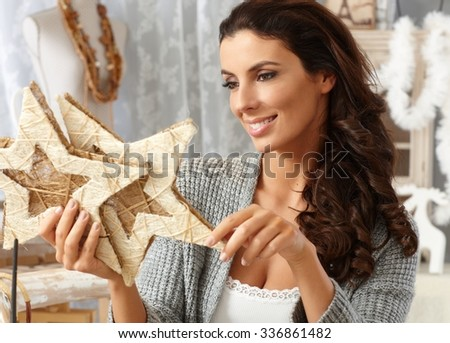 Attractive young woman holding christmas decoration smiling happy. - stock photo