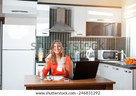 Attractive young woman holding credit card working on finances at home wearing orange pullover sitting at dining table.