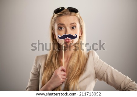 Attractive young woman holding mustache on stick. pretty girl standing on grey background with sunglasses and whiskers - stock photo