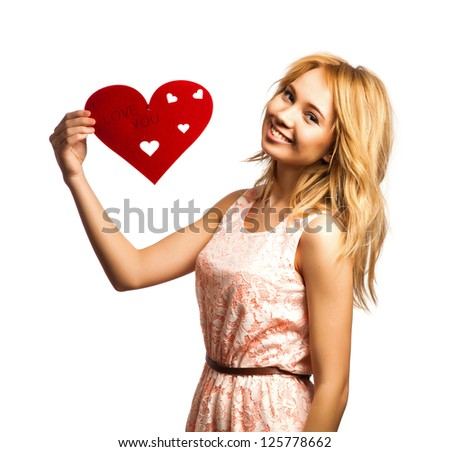 Attractive young woman holding red heart-shape and smiling