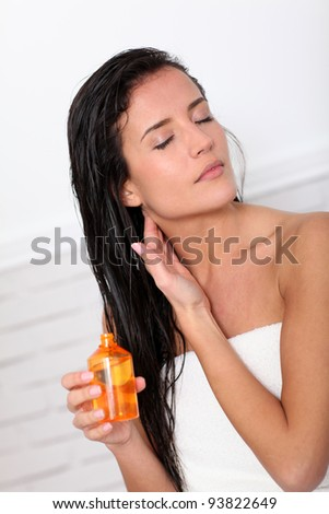 Attractive young woman holding scented oil bottle - stock photo
