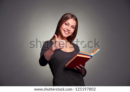 attractive young woman holding the books and showing thumbs up over dark background - stock photo