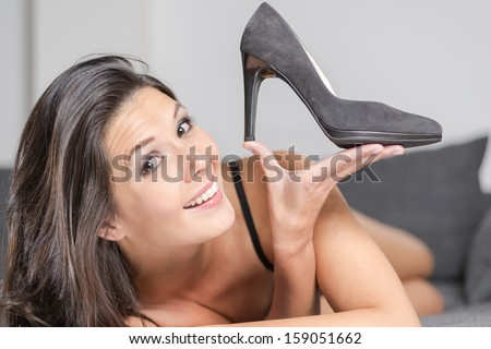 Attractive young woman holding up an elegant high heeled black ladies court shoe in a plush finish, close up of her face and the shoe - stock photo